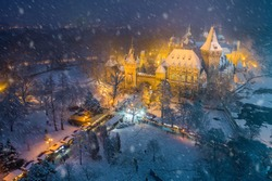 Budapest, Hungary - Christmas market in snowy City Park (Varosliget) from above at night with snowy trees and Vajdahunyad castle