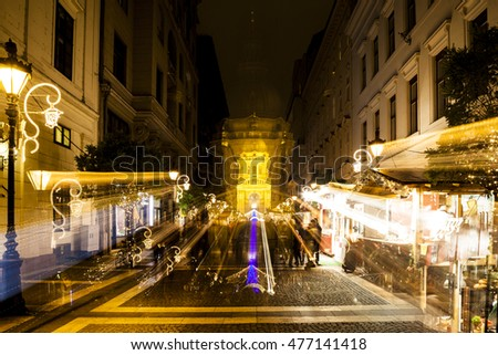 BUDAPEST, HUNGARY - DEC 19 2015: Tourists enjoy the Christmas spirit and the light show in down town Budapest. This traditional Christmas fair attracts over million visitors each year. #477141418