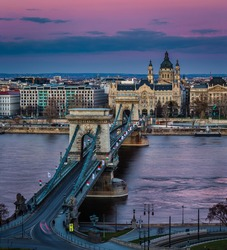 Budapest, Hungary - The famous Szechenyi Chain Bridge (Lanchid) at sunset decorated with national flags celebrating the 15th of March 1848 civic revolution day. St.Stephen's Basilica and magenta sky
