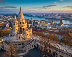Budapest, Hungary - The main tower of the famous Fisherman's Bastion (Halaszbastya) from above with Parliament building and River Danube at background on a sunny morning