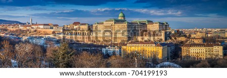 Budapest, Hungary - Ultra wide panoramic skyline view of the beautiful Buda Castle Royal Palace with parliament of Hungary at sunset with blue sky and clouds