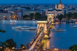 Budapest urban scape with the Basilica and the illuminated Chain Bridge across the Danube River by night.