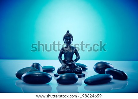 Buddah in a circle of hot stones Wellness and Spa Image, works perfect for advertising Health and Beauty, Spirituality or Massage.