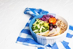 Buddha Bowl. Buckwheat, baked lean pork, red cabbage, cucumber, tomato, olives, flax seeds. Healthy food concept, white putty background, place for text