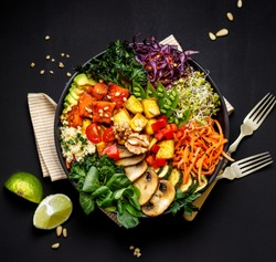 Buddha bowl of mixed vegetables, tofu cheese and groat on a black background, top view. Gourmet and nutritious vegan meal. Healthy eating concept