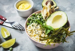 Buddha bowl recipe with quinoa, avocado, lentils, mushrooms, sea kale on concrete background