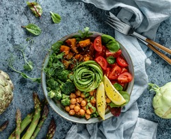 Buddha bowl salad with baked sweet potatoes, chickpeas, broccoli, tomatoes, greens, avocado, pea sprouts on light blue background with napkin. Healthy vegan food, clean eating, dieting, top view
