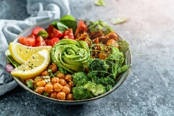 Buddha bowl salad with baked sweet potatoes, chickpeas, broccoli, tomatoes, greens, avocado, pea sprouts on light blue background with napkin. Healthy vegan food, clean eating, dieting, close up