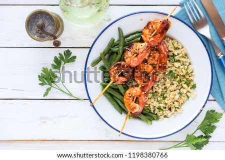 Buddha bowl with brown rice, green beans and shrimp skewers on white wooden table. Overhead view with copy space