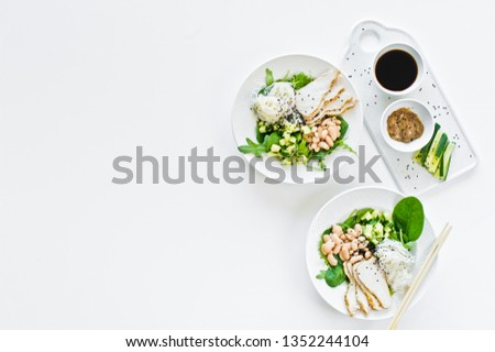Buddha bowl with glass noodles, beans, chicken breast, spinach, arugula and cucumber. White background, top view, space for text