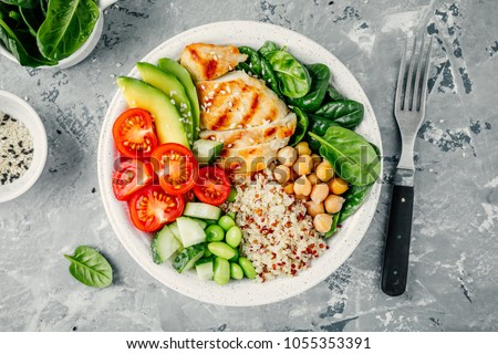 Buddha bowl with spinach salad, quinoa, roasted chickpeas, grilled chicken, avocado, tomatoes, cucumbers, sesame seeds. Top view
