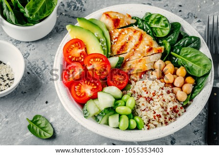 Buddha bowl with spinach salad, quinoa, roasted chickpeas, grilled chicken, avocado, tomatoes, cucumbers, sesame seeds.