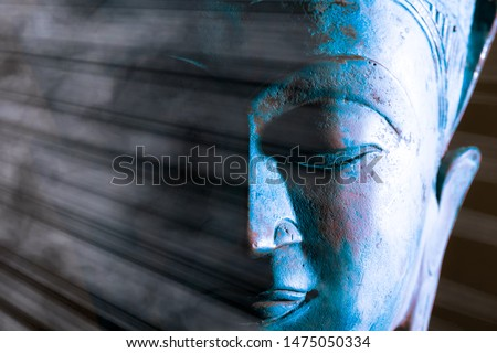 Buddha face close-up. Spiritual enlightenment. Zen Buddhism. Traditional Thai statue with ethereal light. Peaceful blue tone meditation image. Awakening the mind of self with Buddhist mindfulness. #1475050334