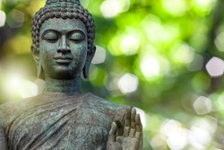 Buddha face, The Buddha statue is made of gold, bronze. On natural bokeh background