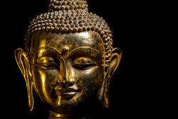 Buddha head with a smiling face and a black background.
