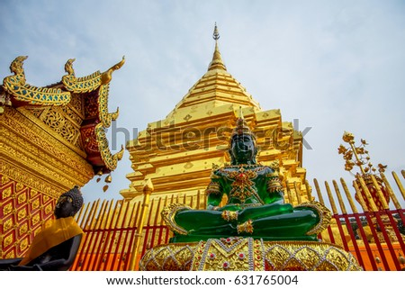 Buddha image and golden pagoda background at the beautiful temple in Thailand.