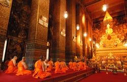 Buddha image and monks in Wat Pho Temple, Bangkok, Thailand