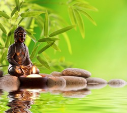 Buddha in meditation with burning candle,bamboo leaf and zen stones.