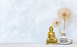 Buddha, pyramid of pebbles, burning candle and dandelion flowers as zen background