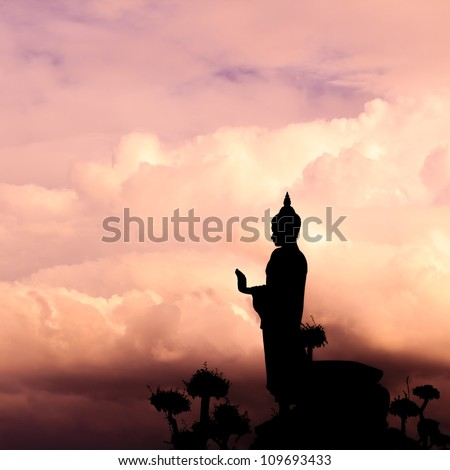 Buddha silhouette on sunset sky.
