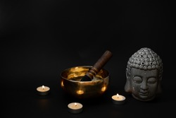 Buddha statue, a singing bowl, and candles on a black background. Calm religious atmosphere.