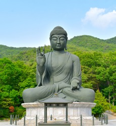 Buddha statue at a Korean Buddhist temple with forests and blue skies in the background in South Korea