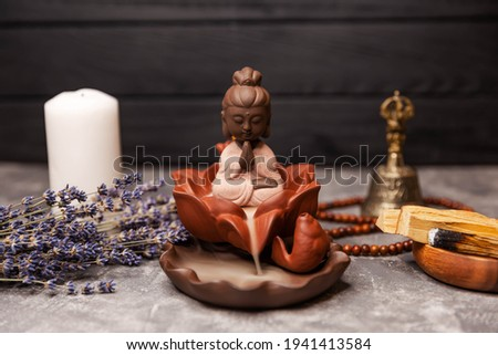 Buddha statue in the smoke of incense on black. Candle incense. Calming zen interiors with buddha statue. Buddha meditation. Aromatherapy, spa table setting with buddha. Lighting perfumed candles.