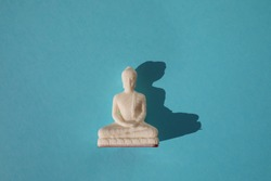 Buddha statue on blue background with copy space. Essential accessory for mindfulness or meditation. Isolated.