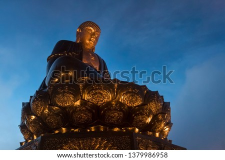 Buddha statue on top at sunset in the clouds. Big buddha statue at the top of Fansipan mountain, Sapa, Lao Cai, Vietnam. Spectacular Fansipan Legend