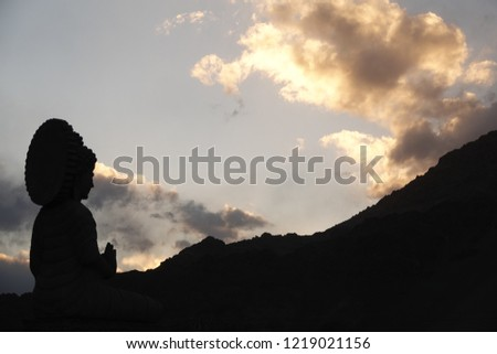 Buddha statue silhouette in the mountains #1219021156