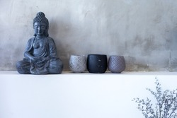 Buddha statue sitting in meditation on gray background