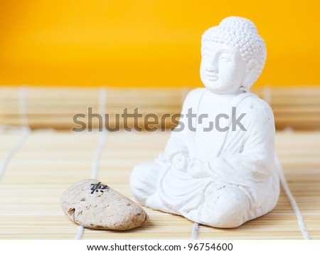 Buddha statue with a stone on a bamboo mat