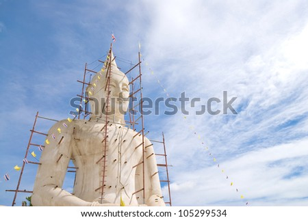 Buddha statue with blue sky and clouds under construction