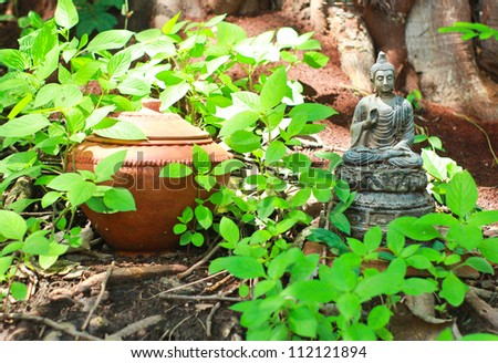 Buddha statue with pot in garden
