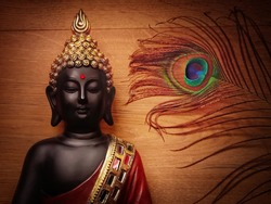 Buddha statue with wooden background and peacock feather/wallpaper image with peacock feather and smiling buddha/peaceful image of buddha meditating with wooden backdrop
