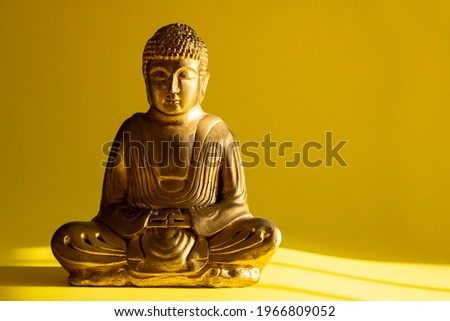 Buddhism and meditation concept: Golden sitting Buddha statue on yellow background with copy space. Zen-like spirituality. Religious sculpture. Travel destination. Decorative object. Photo stock ©