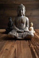 Buddhism concept image. Buddha statue on rustic wooden table.