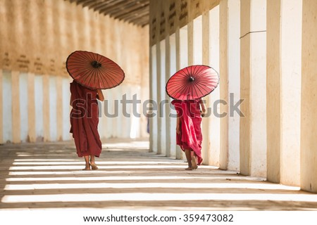 Buddhism novices are walking with umberella in temple