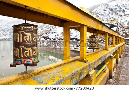 Buddhism prayer wheels on a bridge over Lake Changu in Sikkim, India