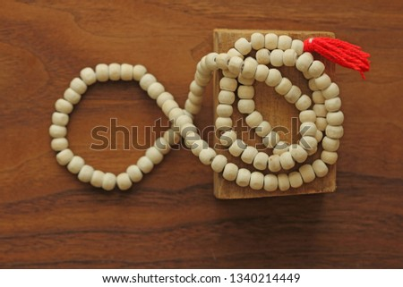 Buddhist beads. Rosary or beads from the sacred tree of Tulasi with a red tassel. #1340214449
