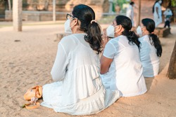Buddhist Female devotees worshipping at Jaya Sri Maha Bhodi while sitting on the sandy soil in white dresses. Concept of new normal, wearing a face mask while chanting prayers.