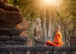 Buddhist monk and novice meditation in front of the Buddha statue at the old temple