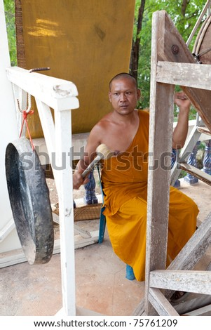 Buddhist monk, hitting the drum in the temple - stock photo