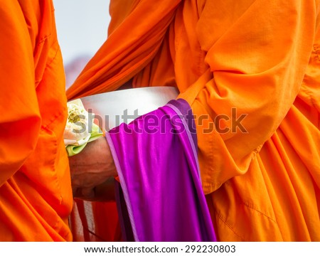 Buddhist monk holding alms bowl and lotus flower in religious concept