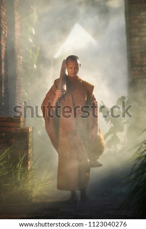 Buddhist monk walking under morning light at Ayutthaya Province, Thailand.