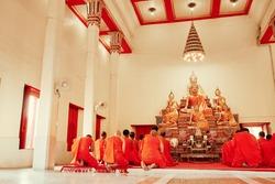 Buddhist monks kneels down prayer in temple Wat Chalong, Phuket, Thailand.