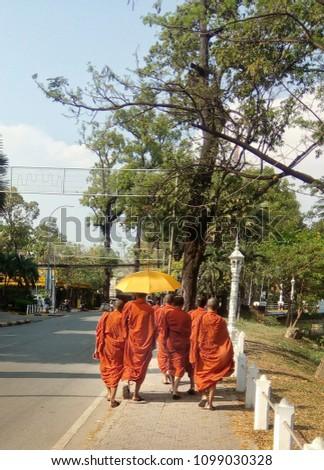 Buddhist monks walking under yellow umbrella #1099030328