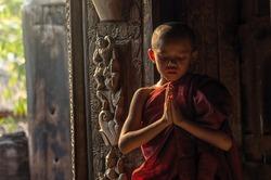 Buddhist novice praying at Shwenandaw pagoda, mandalay, myanmar