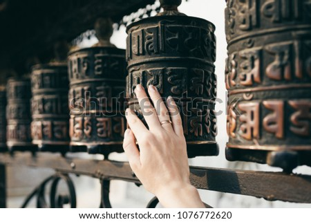 Buddhist prayer drums with close-up mantras.The female hand touches the Buddhist prayer drum, Nepal.The interaction of human energy and the Buddhist prayer drum.the girl turns the prayer drum.