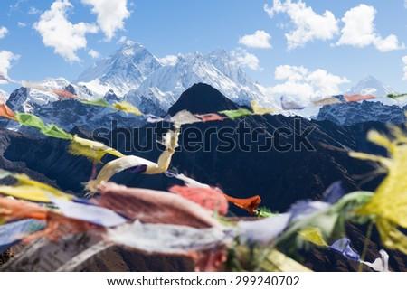 Buddhist prayer flags, Gokyo Ri mountain summit peak, snow mountains peaks. Everest Base Camp trail route, trekking Nepal culture, Himalaya ridge traveling.